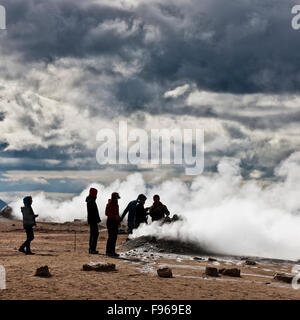 Tourists at geothermal hot springs, Hverarond, Namaskard, Iceland. The area is characterized by boiling mud-bogs - Stock Photo