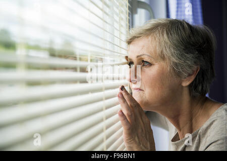 Scared woman is looking through the window. Having bruise on her face - Stock Photo