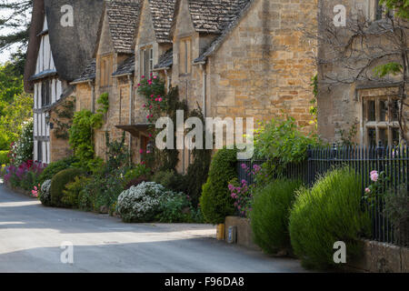Colourful summer flowers and fine stone houses line a quiet street in the Cotswolds village of Stanton, Gloucestershire, - Stock Photo