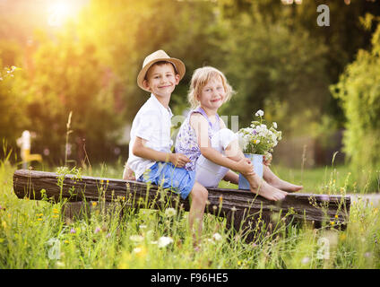 Cute boy and girl in love. They sitting on bench at sunset. - Stock Photo