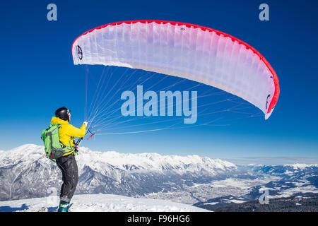 Paraglider, man preparing glider for takeoff, Axamer Lizum, Innsbruck, Tyrol, Austria - Stock Photo