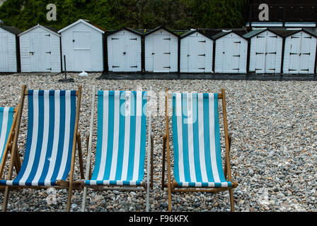 Striped deck chairs and beach huts on Beer beach, Devon, England UK - Stock Photo
