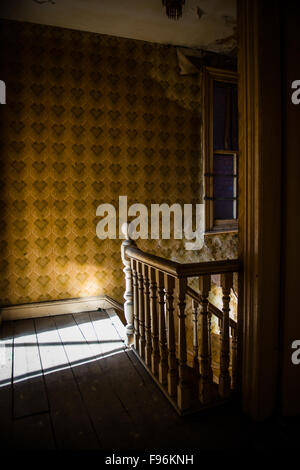 A derelict abandoned  uninhabited building interior room with peeling wallpaper and plaster falling off the walls, - Stock Photo