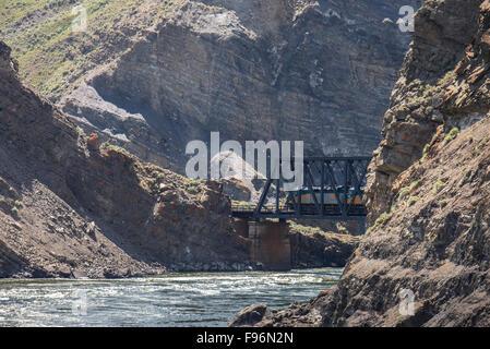 Train locomotive going over a trestle bridge in the Black Canyon near Ashcroft, British Columbia, Canada. - Stock Photo