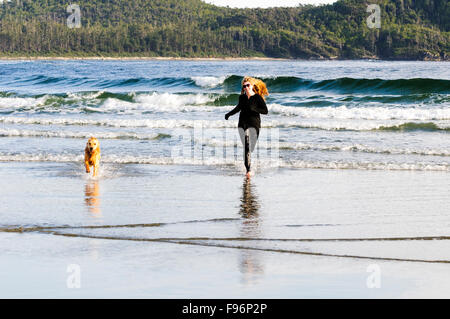 A young woman running with her Golden Retriever on Chesterman Beach near Tofino British Columbia. - Stock Photo