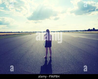 Rear View Of Woman Standing On Country Road Against Cloudy Sky - Stock Photo