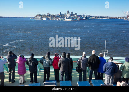 Passengers on the top deck of a cruise ship watching as their vessel makes its way towards Quebec City in the distance - Stock Photo