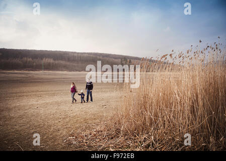 Happy young family spending time together in nature. - Stock Photo