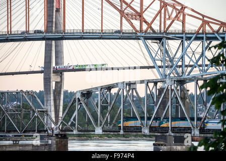 Pasenger train going over a bridge, Vancouver Skytrain going over the Skytrain bridge, and cars going over the Patullo - Stock Photo