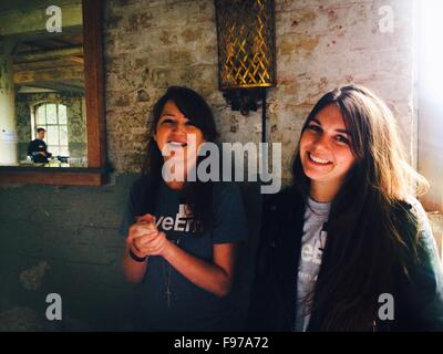 Portrait Of Friends Smiling While Standing Against Wall - Stock Photo