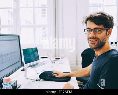 Portrait Of A Man Working On Computer In Office - Stock Photo