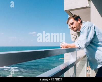 Man Looking Away While Leaning On Railing