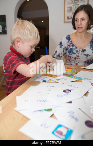 Five year old boy writing his Christmas cards to classmates and school friends, UK - Stock Photo