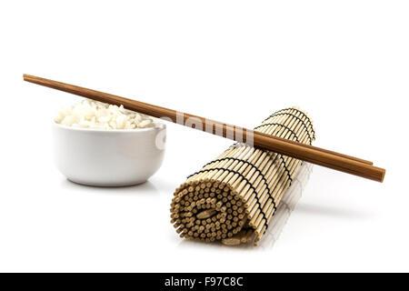 Bowl of rice and chopsticks on bamboo mat - Stock Photo