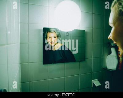 Reflection Of Beautiful Woman On Mirror In Bathroom - Stock Photo