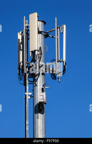 Cell tower and radio antenna for mobile phone network on a blue sky - Stock Photo