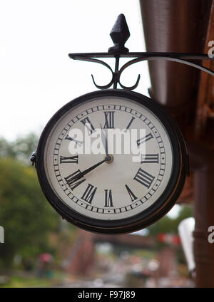 Classic vintage clock at old railway station with rain on clock face - Stock Photo