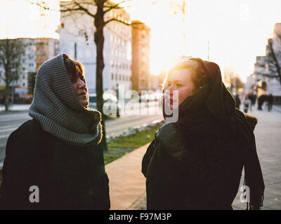 Young Female Friends Standing On Street In City - Stock Photo