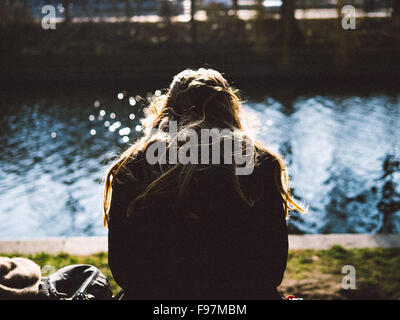 Rear View Of Woman Relaxing On Riverbank - Stock Photo