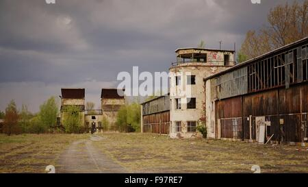 Road By Old Factory Against Cloudy Sky - Stock Photo