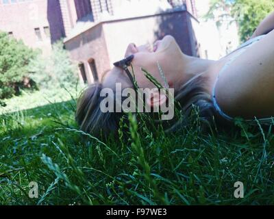 Side View Of Smiling Woman Lying Down On Grass At Park - Stock Photo