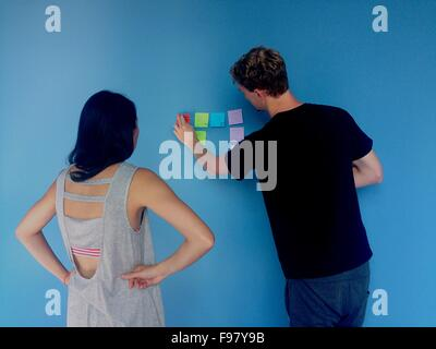 Man Sticking Adhesive Notes On Blue Wall By Woman - Stock Photo