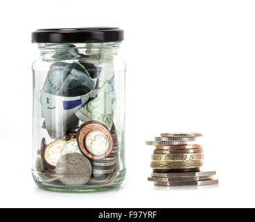Glass jar with coins and notes from around the world on a white background - savings concept - Stock Photo