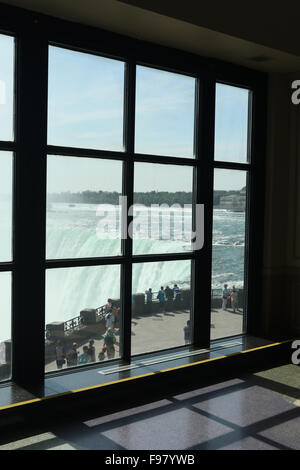 Tourists at the rail. View from window in Table Rock House Visitors Center. Canadian Falls. Horseshoe Falls. Niagara - Stock Photo