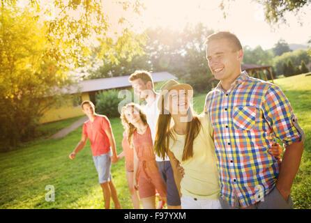 Group of six teenage friends having fun in park - Stock Photo