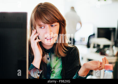 Worried Woman Talking On Mobile Phone While Sitting At Computer Desk In Office - Stock Photo
