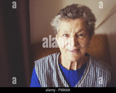 Portrait of senior woman sitting in armchair at home - Stock Photo