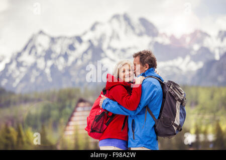 Senior hikers couple kissing during the walk in beautiful mountains, hills and hotel in background - Stock Photo