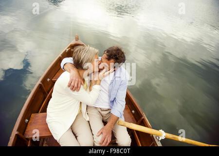 Senior couple kissing on boat on mountain tarn - Stock Photo