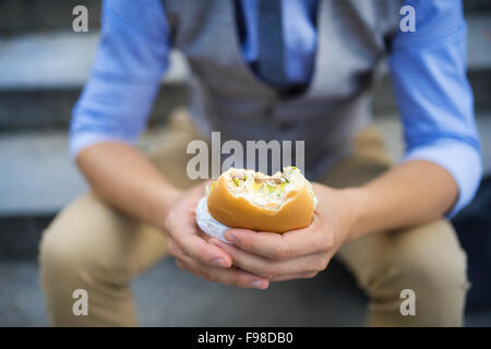Deatil of modern hipster businessman having lunch break, sitting on stairs in town center and eating burger - Stock Photo