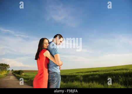 Happy young couple in love hugging on countryside road next to the colza field - Stock Photo