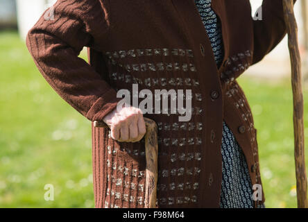 Detail of very old woman's hands holding walking stick - Stock Photo