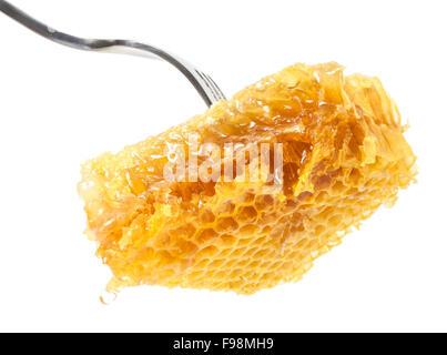 Fresh Honeycomb on fork close up on white background - Stock Photo