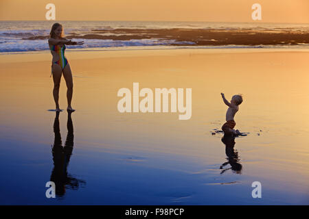Silhouette with black shadows of mother with baby running on wet gold sunset sand to sea surf to swim in beach wave. - Stock Photo