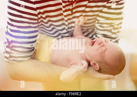 Young father holding his crying newborn baby girl - Stock Photo