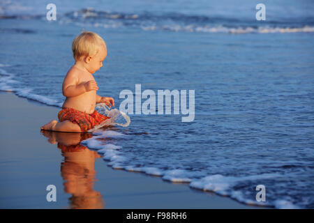On sunset beach happy baby swimmer sit on black sand and look at sea surf with foam and splash for swimming in waves. - Stock Photo