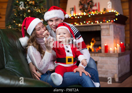 Happy family with kid weared Santa sitting on sofa in front of Christmas tree and fireplace  in living room - Stock Photo