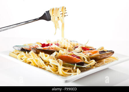 Pasta with mussels on white dish - Italian food - Stock Photo