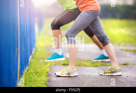Young couple stretching after the run on asphalt in rainy weather. Details of legs. - Stock Photo