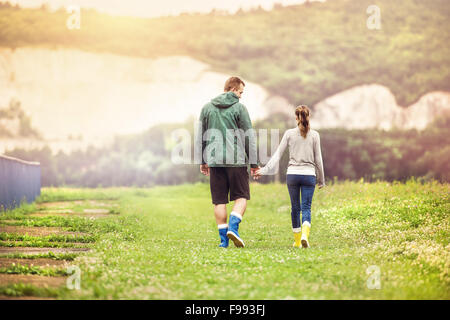 Young couple in colorful wellies walking in muddy nature. - Stock Photo