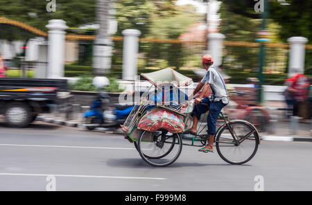 YOGJAKARTA, INDONESIA - AUGUST 21, 2015: panning shot of people riding in a becak through the streets of Yogyakarta. - Stock Photo