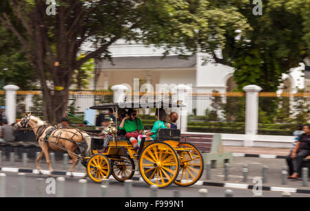 YOGJAKARTA, INDONESIA - AUGUST 21, 2015: panning shot of tourists riding in a horse cart in the streets of Yogyakarta. - Stock Photo
