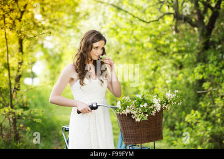 Pretty young woman with retro bike in green park - Stock Photo