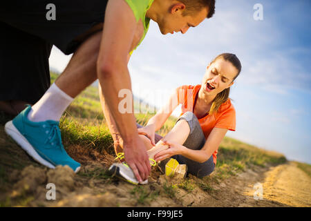 Injury - sports woman with twisted sprained getting help from man touching her ankle. Stock Photo