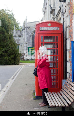 Lady in a red winter coat stood by a red telephone box waiting for a local bus - Stock Photo