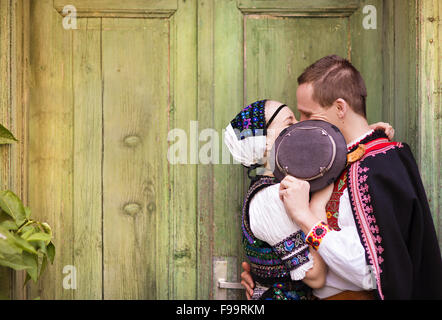 Love couple standing by the door wearing national Eastern Europe folk costumes. - Stock Photo